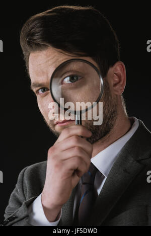 portrait of businessman holding magnifying glass isolated on black - Stock Photo