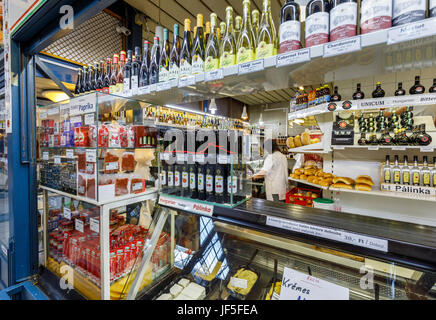 Stall in the covered Central Market Hall (Vasarcsarnok), display of bottles of traditional fruit flavoured palinka - Stock Photo
