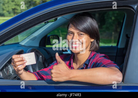 Young woman showing driving license in car - Stock Photo