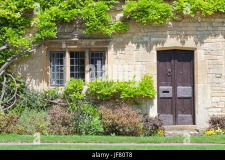 Dark brown old doors intraditional English stone house with climbing wisteria on the wall, flowers and herbs in - Stock Photo