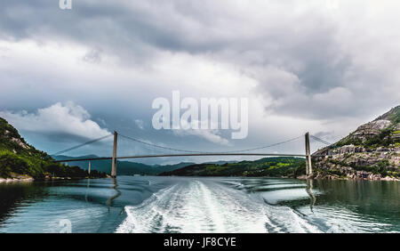 The bridge connecting the shore of the fjord in Norway on the background of dramatic sky and the waves from the - Stock Photo