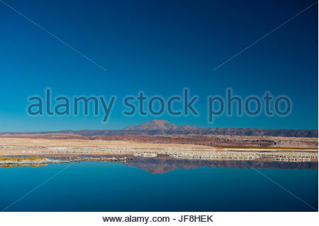 A landscape view of salty Tebenquiche Lake and distant mountain peaks. - Stock Photo