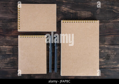 Set of three spiral notepads with two black pens on wooden table. Top view with copy space - Stock Photo