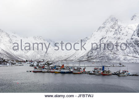 A harbor in Austnes Fjord and snow-covered mountains. - Stock Photo