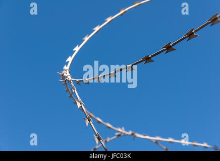 Barbed wire against the blue sky - Stock Photo