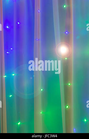 Christmas lights in the window on the background of transparent tulle. - Stock Photo