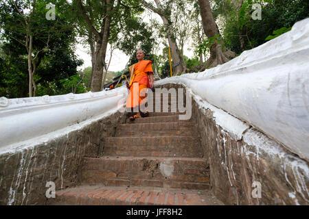 Buddhist monk walking down the Thanon Phousi staircase on the Mount Phou Si, Luang Prabang, Laos, Asia - Stock Photo