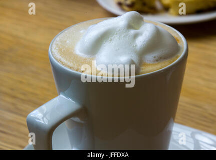 A large frothy topped hot cappuccino coffee in a plain porcelain cup. - Stock Photo