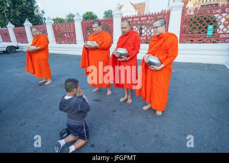 Thailand, Bangkok, Wat Benchamabophit aka The Marble Temple, Child Praying to Monks - Stock Photo