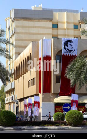 Doha, Qatar. 1st July, 2017. Qatari flags emblazoned with images of Emir HH Tamim bin Hamad al-Thani fly from a - Stock Photo