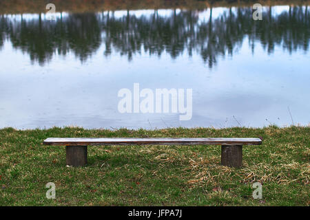 Lonely empty wooden bench by the lake - Stock Photo