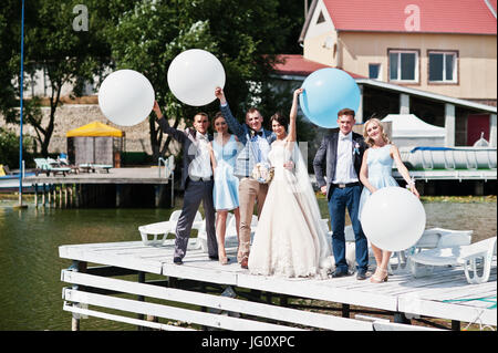 Wedding couple, groomsmen and bridesmaids having fun with balloons on wharf. - Stock Photo
