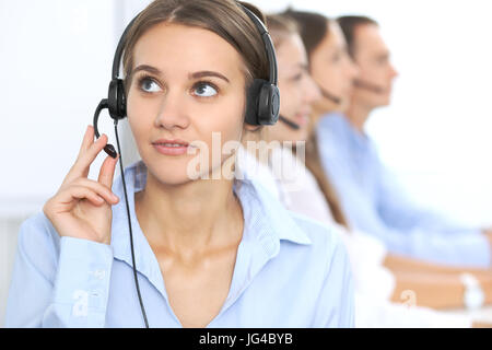 Call center operator in headset while consulting client. Telemarketing or phone sales. Customer service and business - Stock Photo