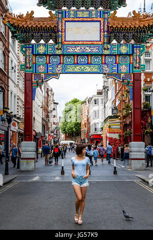 A Young Japanese Tourist Poses For A Photo Under The New Chinatown Gate On Wardour Street, Entrance To Chinatown, - Stock Photo