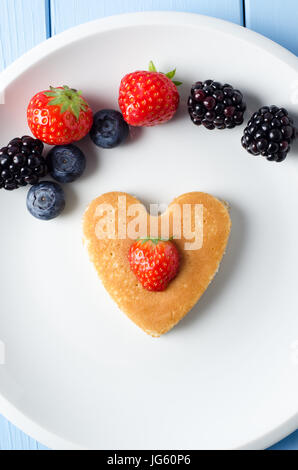 A heart shaped pancake in the middle of a white plate, with a strawberry centred on top of it.  Above it, a variety - Stock Photo