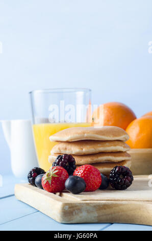 A kitchen table setting with pancakes stacked on wooden chopping board surrounded by Summer fruits, a glass of orange - Stock Photo