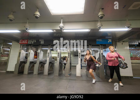 Passengers swipe through the turnstiles in the newly restored South Ferry subway station in New York on re-opening - Stock Photo