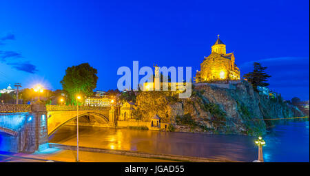 The rocky hill topped with Metekhi Church and Vakhtang Gorgasali monument looks great in bright evening lights, - Stock Photo