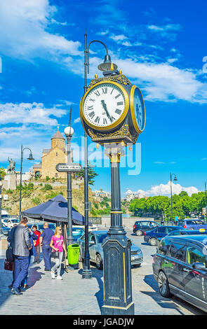 TBILISI, GEORGIA - JUNE 5, 2016: The old lamp post clock in Vakhtang Gorgasali square with a view on Metekhi church - Stock Photo