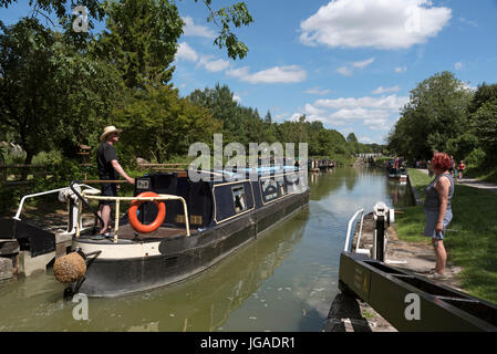 Holiday rental canalboat exiting a lock  on the Kennet & Avon Canal close to Devizes in Wiltshire England UK. - Stock Photo