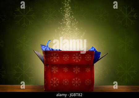 An opened red Christmas gift box with gold snowflake patterns, emitting a magical warm bright glowing light and - Stock Photo