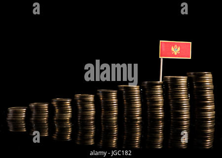 Montenegrin flag with lot of coins isolated on black background - Stock Photo