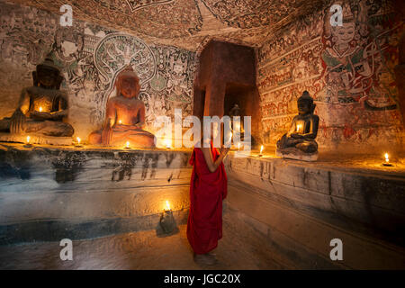 Monk praying with candle light at Po Win Taung / Hpowindaung cave - Monywa - Sagaing region - Northern Myanmar - Stock Photo