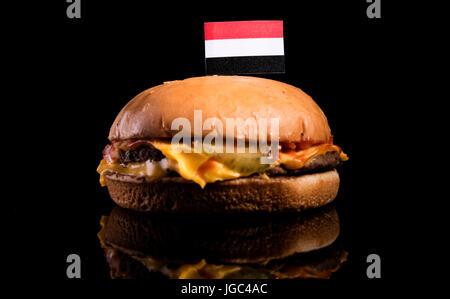 Yemeni flag on top of hamburger isolated on black background - Stock Photo