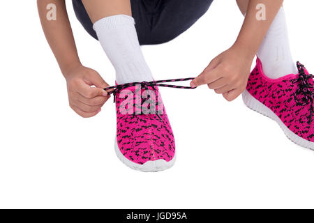 Closeup on kid hands tying her shoes in isolated white background - Stock Photo