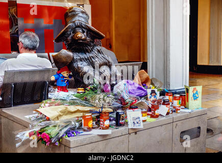 Jars of marmalade, cards and flowers laid at statue of Paddington Bear, at Paddington station, following the death - Stock Photo