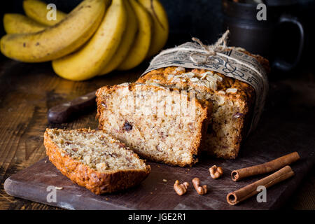 Sliced banana bread loaf with walnuts and cinnamon on wooden board. Closeup view - Stock Photo