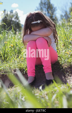 Sad girl sitting in parkland on a sunny day - Stock Photo