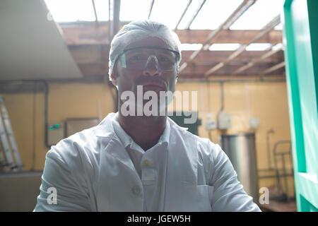 Portrait of scientist standing at doorway in warehouse - Stock Photo