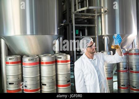 Scientist examining beer in beaker at warehouse - Stock Photo
