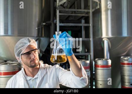 Scientist examining beer in beaker at factory - Stock Photo