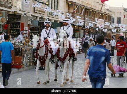 DOHA, QATAR - JULY 6, 2017: Mounted police pass under bunting expressing loyalty to Qatari Emir Sheikh Tamim bin - Stock Photo