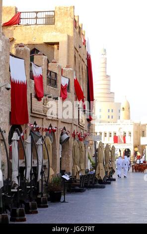 DOHA, QATAR - JULY 6, 2017: Flags hung from restaurants in Souq Waqif market express  loyalty to Qatari Emir Sheikh - Stock Photo