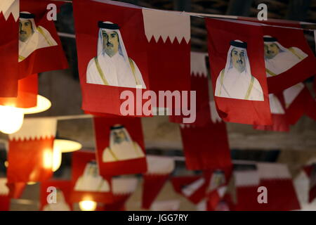 DOHA, QATAR - JULY 6, 2017: Ntional flags printed with images of Qatari Emir Sheikh Tamim bin Hamad al-Thani are - Stock Photo