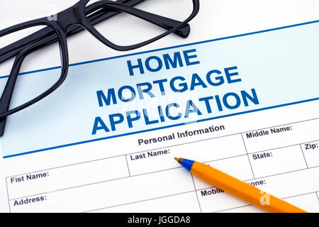 Home Mortgage Application with ballpoint pen and glasses. - Stock Photo