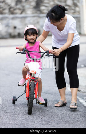 Asian Chinese little girl riding bicycle with mom guide on tar road outdoor. - Stock Photo