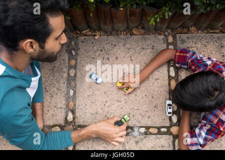 High angle view of father and son playing with toy car in yard - Stock Photo
