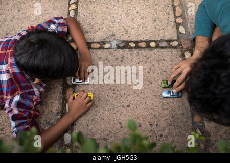 High angle view of son and father playing with toy car in yard - Stock Photo