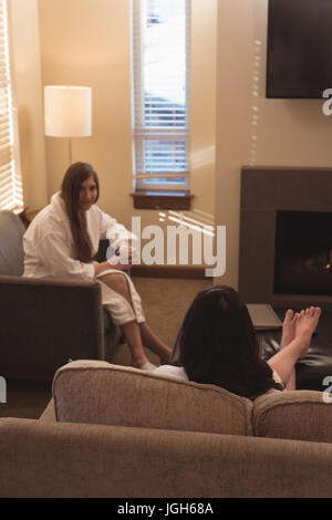 Female friends interacting with each other in the living room at home - Stock Photo