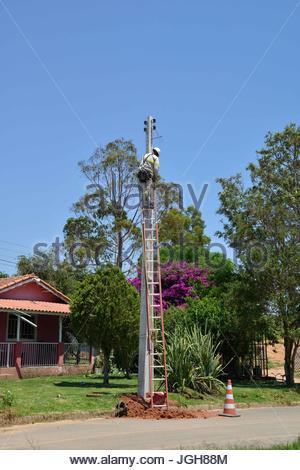 Worker Energisa Group installing new grid in Geninho neighborhood, Munhoz, Minas Gerais, Brazil. 10.2015 - Stock Photo