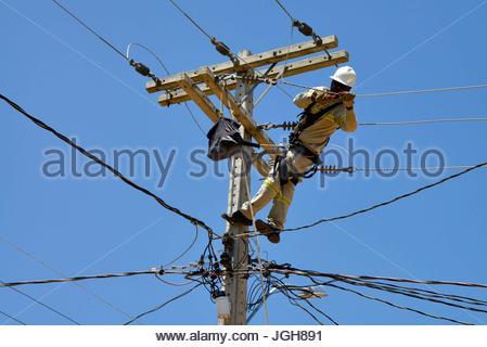Workers Energisa Group installing new grid in Geninho neighborhood, Munhoz, Minas Gerais, Brazil. 10.2015 - Stock Photo