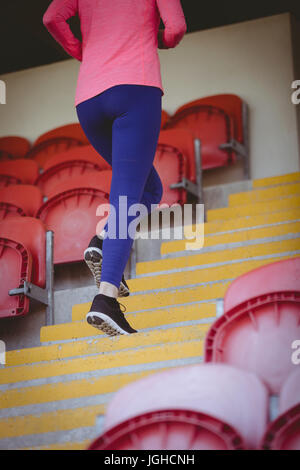 Low section of young female athlete moving up on steps at stadium - Stock Photo