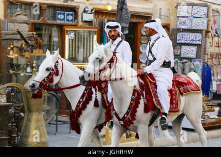 DOHA, QATAR - JULY 6, 2017: Mounted police continue their leisurely patrols of the capital's Souq Waqif market during - Stock Photo