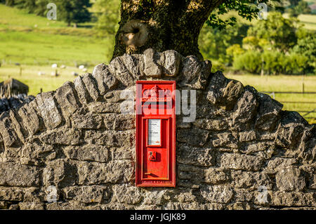 Royal Mail post box in an undulating stone wall, between Castleton and Hope in the Peak District, Derbyshire, England, - Stock Photo