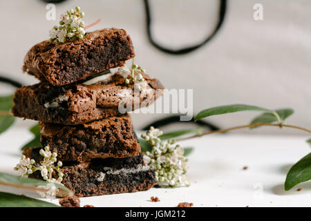 Chocolate brownies, with black biscuit stuffed with cream, stacked - Stock Photo