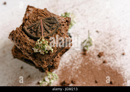 Chocolate brownies, with black biscuit stuffed with cream, stacked, from above - Stock Photo